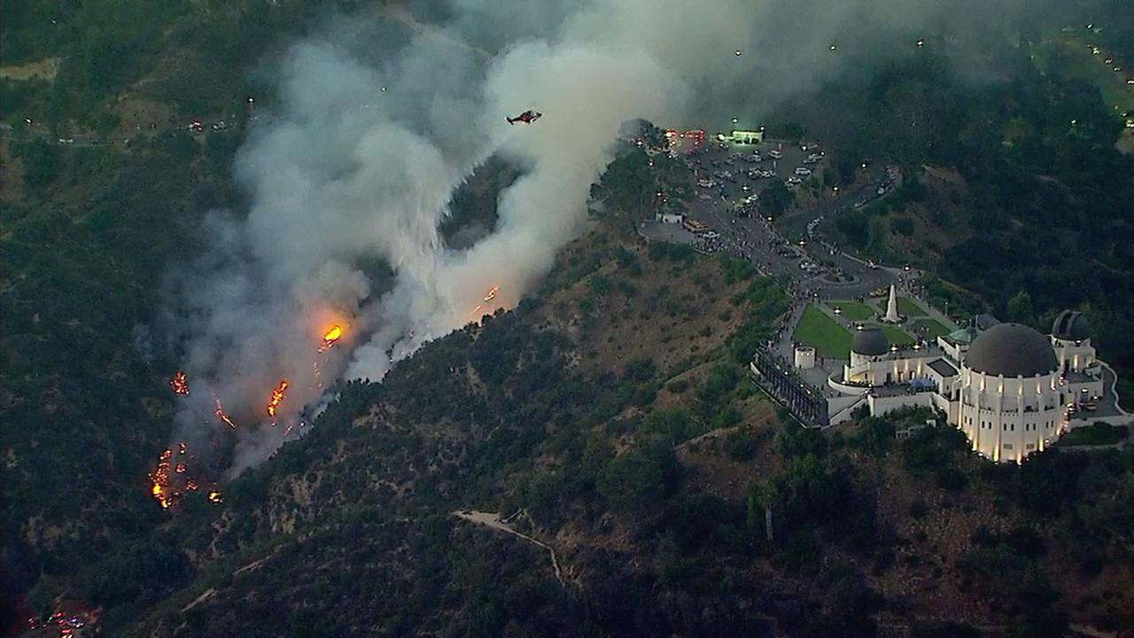 A helicopter dropped water on a small brush fire burning up a hillside near the parking lot of Griffith Observatory in Los Angeles on Tuesday, June 19, 2018.