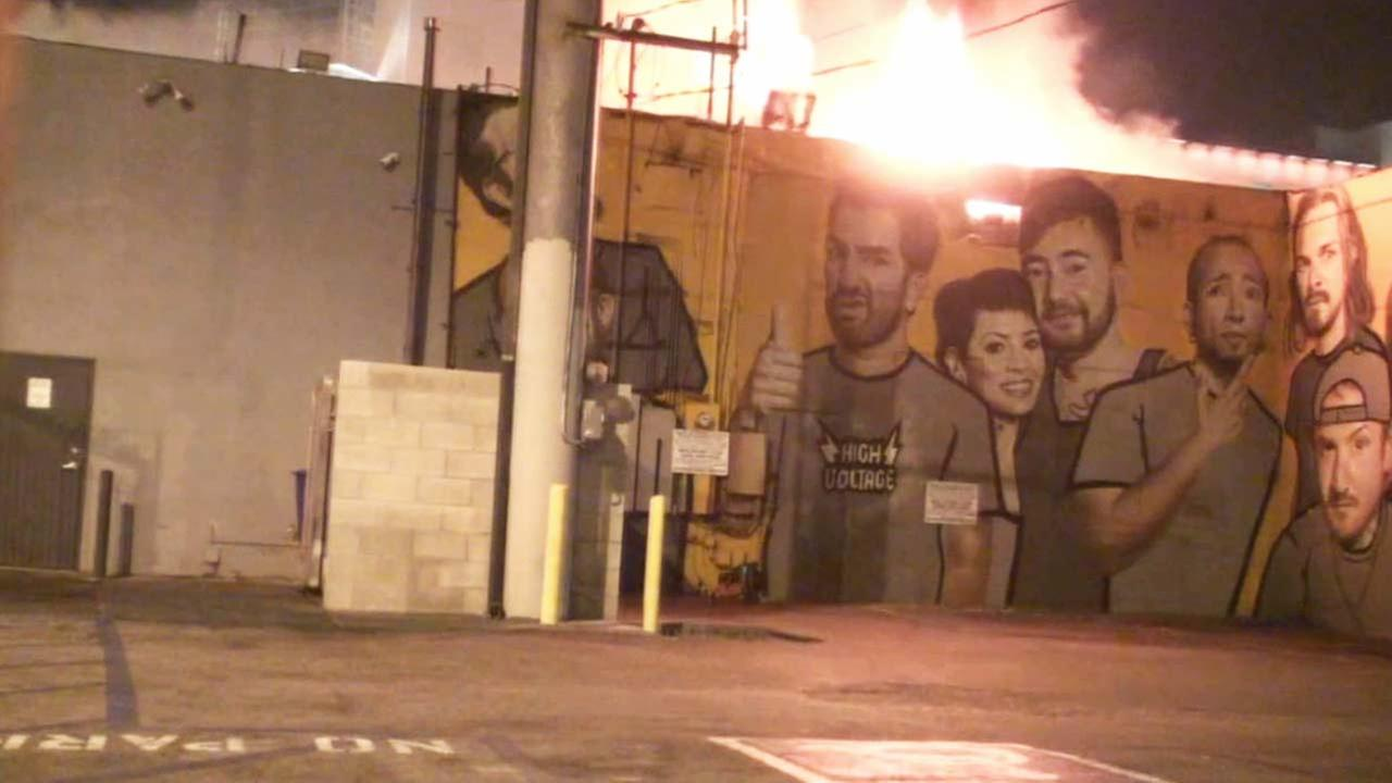 Flames are shown coming out of High Voltage Tattoo in the 1200 block of North La Brea Avenue on Thursday, Oct. 23, 2014.
