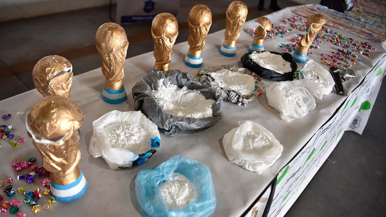 This Thursday, June 21 photo, released by the National Security Ministry shows fake World Cup trophies stuffed with cocaine, and the product itself on display next to the trophies, in Buenos Aires, Argentina.