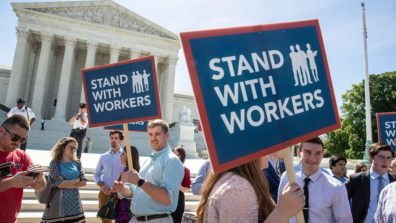 In this Monday, June 25, 2018 photo, people gather at the Supreme Court awaiting a decision in an Illinois union dues case, Janus vs. AFSCME, in Washington.