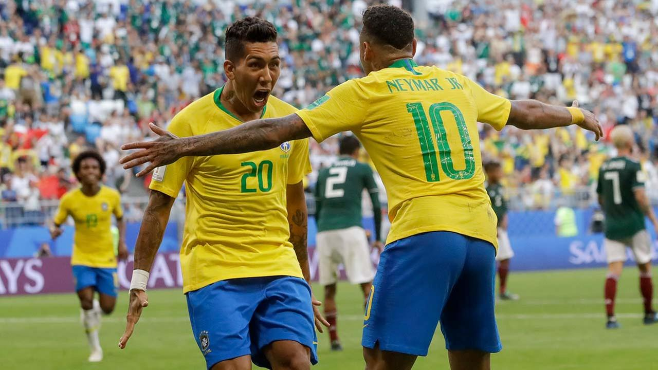 Brazils Roberto Firmino celebrates with Brazils Neymar after scoring during the round of 16 match between Brazil and Mexico at the 2018 World Cup in Russia, Monday, July 2, 2018.