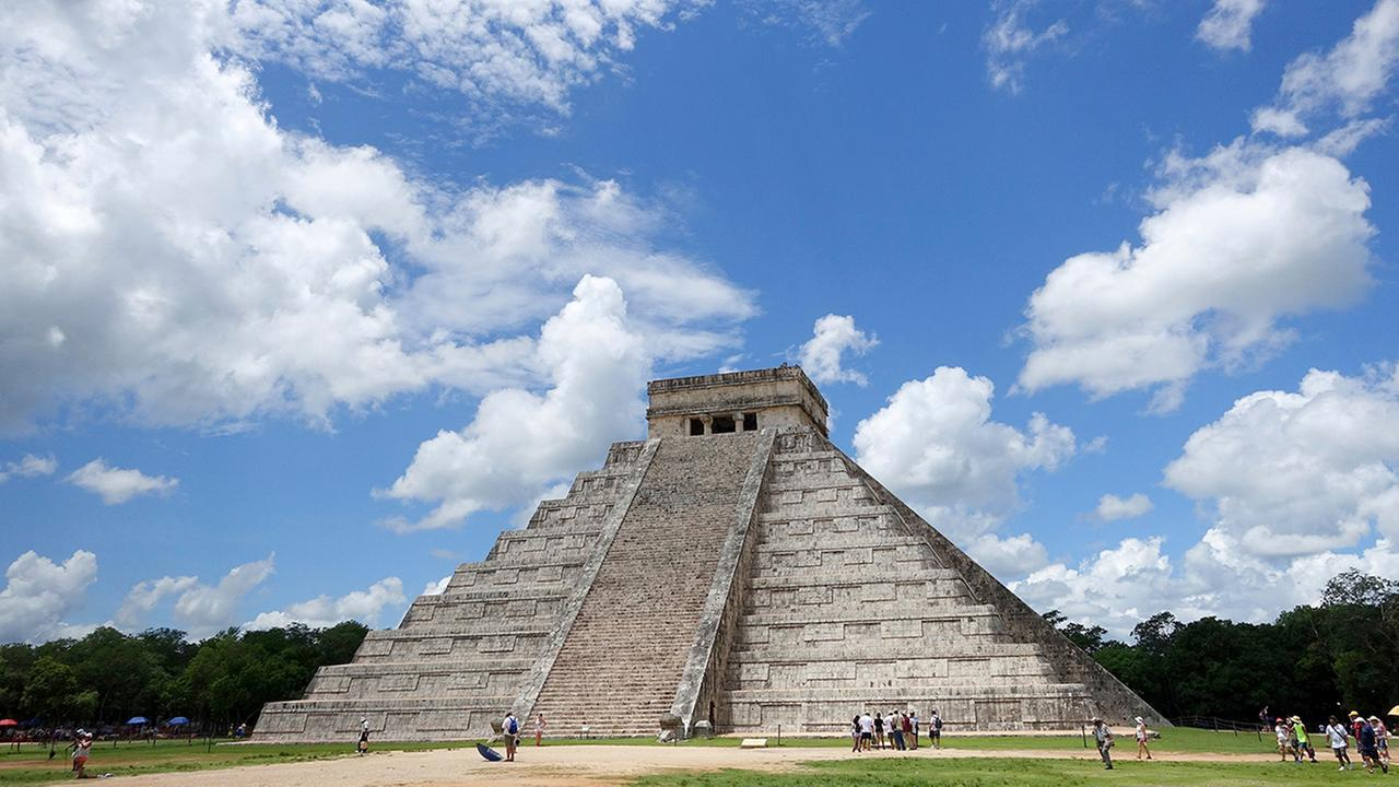 In this July 22, 2016 photo, tourists are dwarfed by El Castillo at the Chichen-Itza ruins in Yucatan, Mexico.