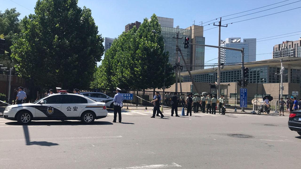 Officials and security personnel stand near the site of a reported blast outside the U.S. Embassy in Beijing, Thursday, July 26, 2018.