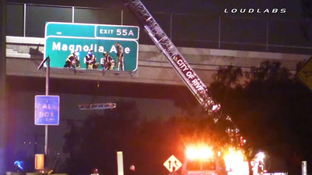 A teenager had to be rescued after climbing a fence on an overpass and falling onto a freeway sign in Riverside on Thursday, Nov. 13, 2014.