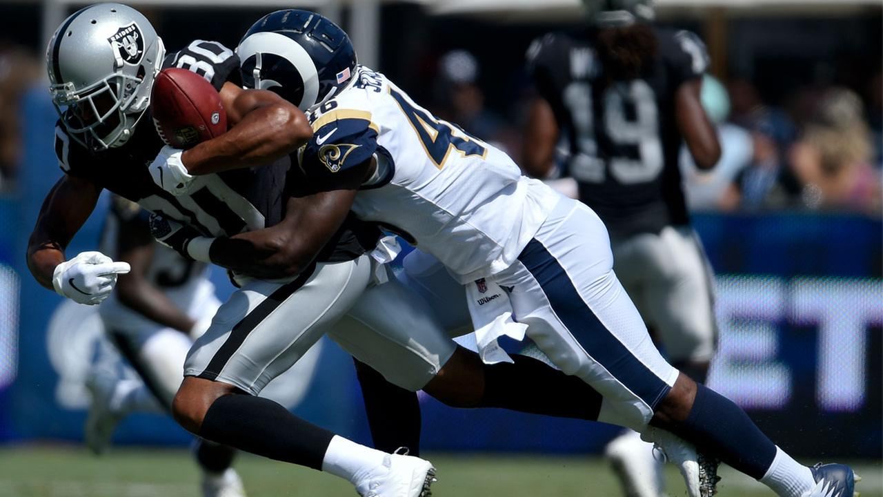 Oakland Raiders wide receiver catches a pass under pressure from Los Angeles Rams linebacker during the second half in an NFL preseason football game.