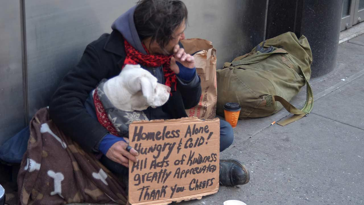 A homeless man sits on the street with a dog and asks for help Feb. 25, 2012 in New York City.