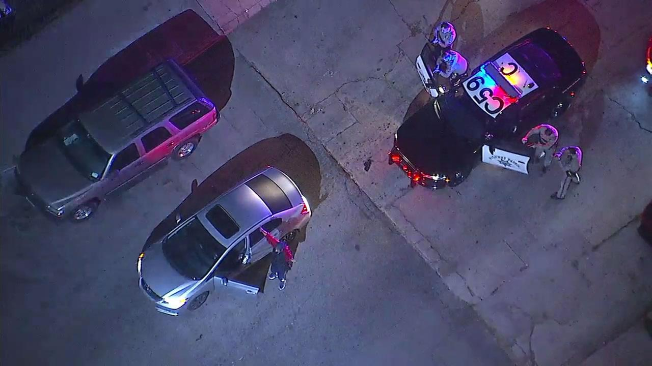 A speeding and reckless driving suspect walks backward toward police after surrendering during a chase in South Los Angeles.