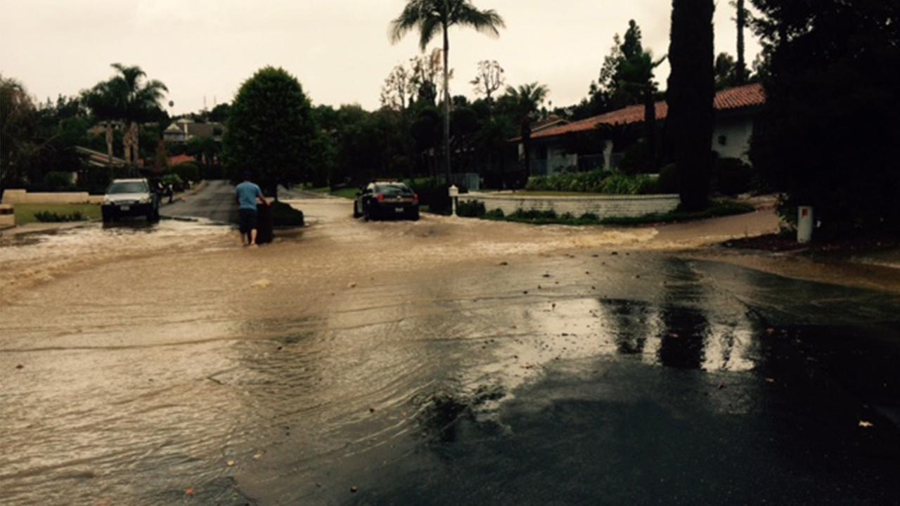 Water floods a street in Villa Park, where a water main broke on Sunday, Nov. 30, 2014.