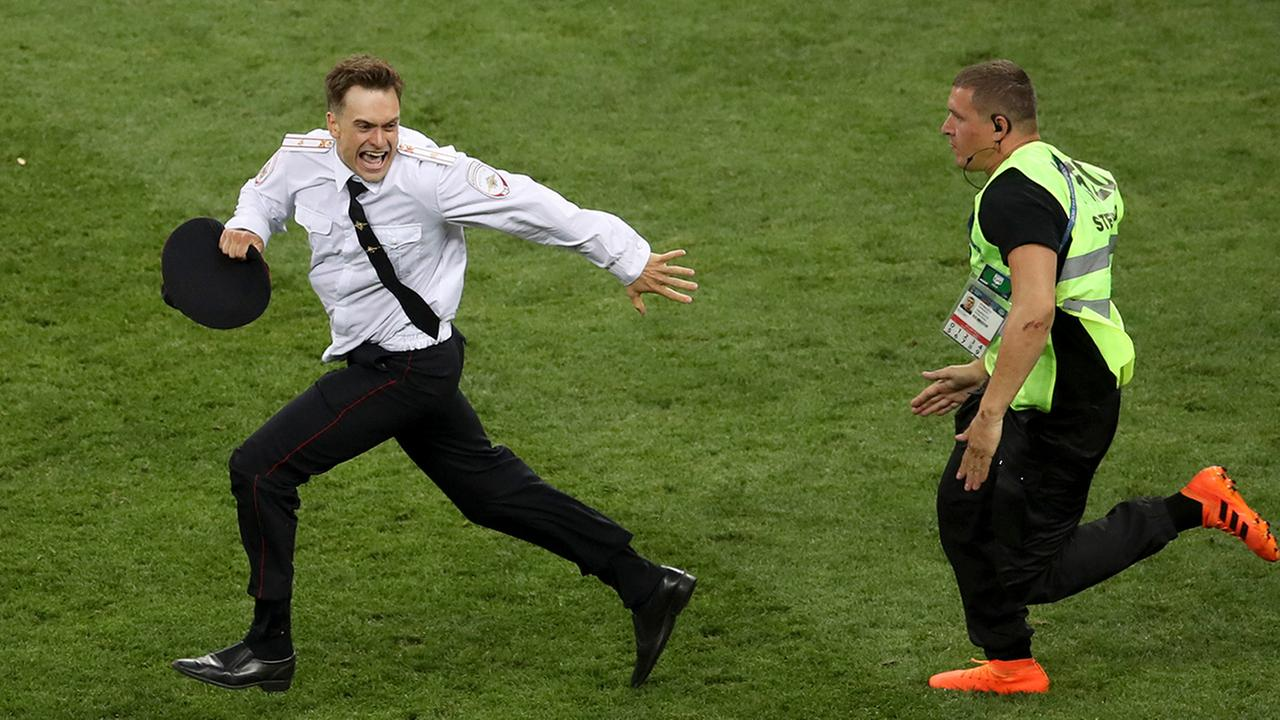 In this Sunday, July 15, 2018 photo, Pyotr Verzilov invading the pitch, runs away as a steward tries to stop him during the France and Croatia 2018 World Cup final match.