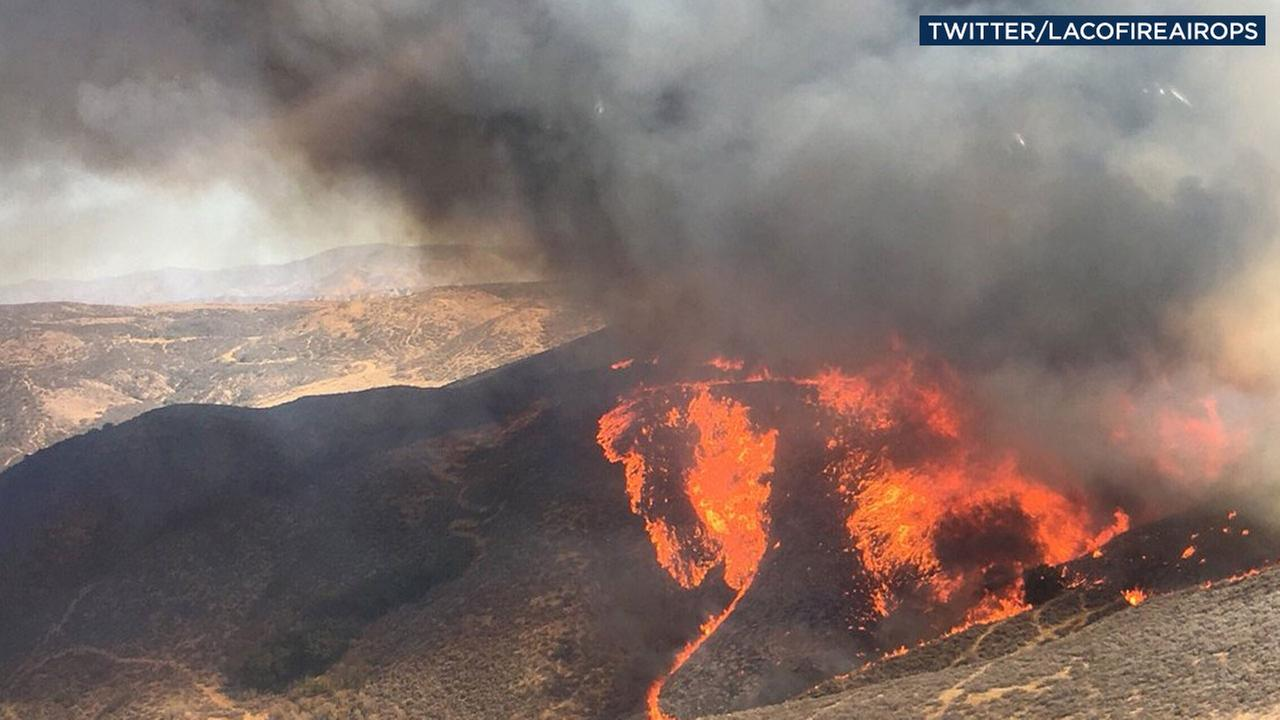 A fire sent up a dark plume of smoke as it charred a hillside near Charlie Canyon Road in Castaic on Saturday, Sept. 22, 2018.