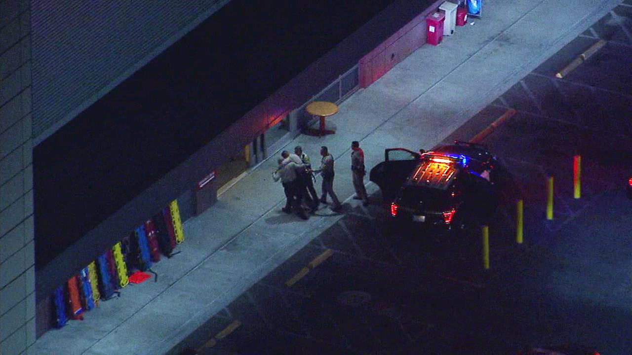 Los Angeles County sheriffs deputies are seen carrying a wounded deputy who was shot in East Los Angeles late Monday, Sept. 25, 2018.