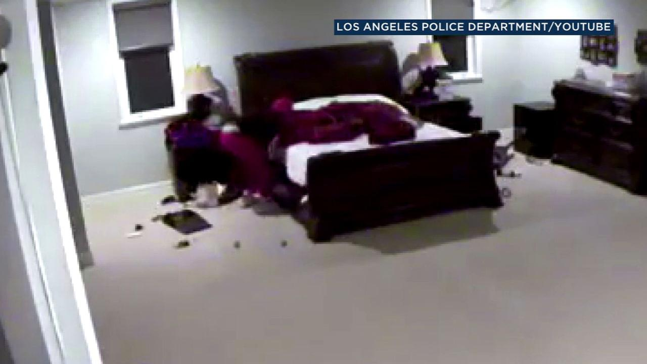 A burglary suspect is shown searching under the bed inside of a room at Los Angeles Dodger Yasiel Puigs Encino home.