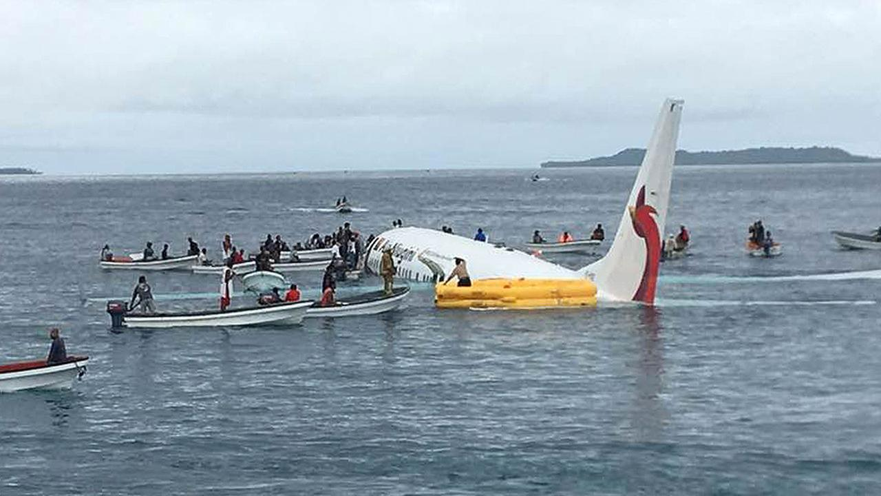 Local fishing boats move in to recover the passengers and crew of Air Niugini flight following the plane crashing into the sea in the Federated States of Micronesia.
