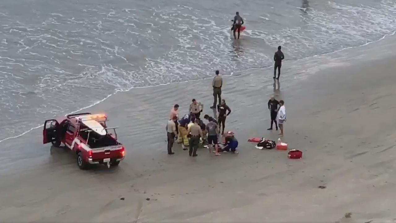 Encinitas lifeguards and San Diego County sheriffs deputies attend to an injured child who was attacked by a shark at Beacons Beach on Saturday, Sept. 29, 2018.