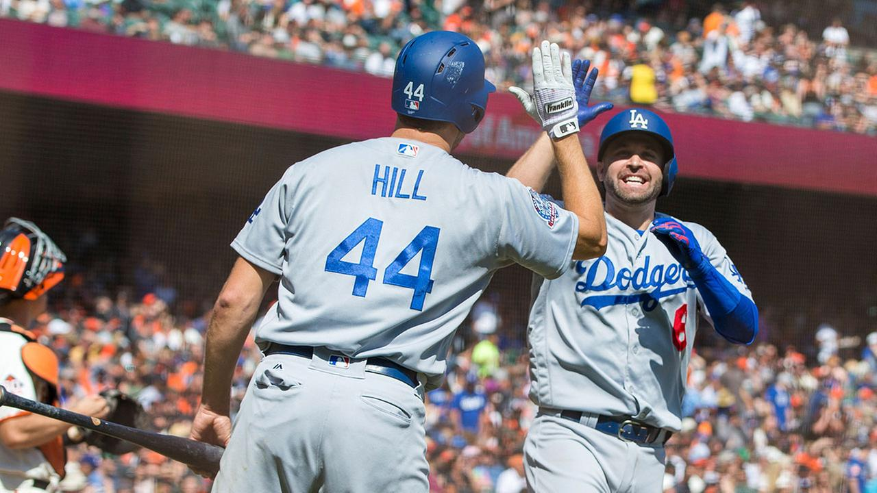 Dodgers Brian Dozier celebrates with Rich Hill after he hit a two-run home run against the Giants in the third inning of a baseball game in San Francisco, Sunday, Sept. 30, 2018.