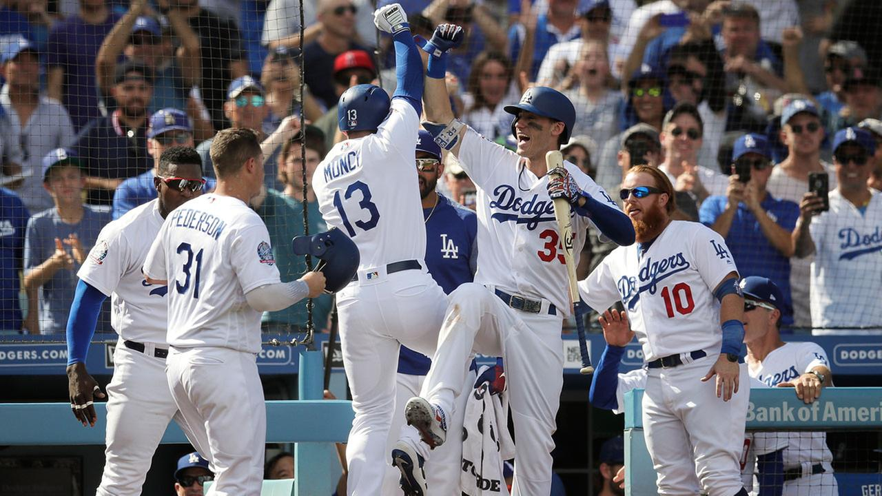 Max Muncy celebrates a two-run home run with Cody Bellinger and other teammates during the Dodgers-Rockies tiebreaker game in Los Angeles on Oct. 1, 2018.