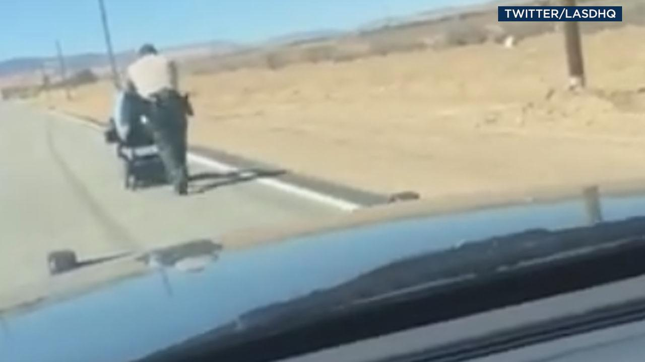 Los Angeles County sheriffs Deputy Montanez pushes a motorized wheelchair back to the owners home because it could not fit in the patrol vehicle.