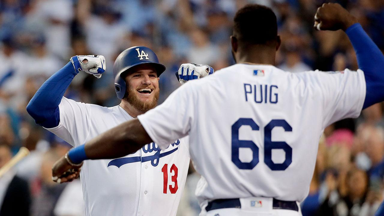 Dodgers Max Muncy and Yasiel Puig celebrate after Muncy hit a home run during Game 1 of the NLDS series against the Atlanta Braves on Oct. 4, 2018 in Los Angeles.