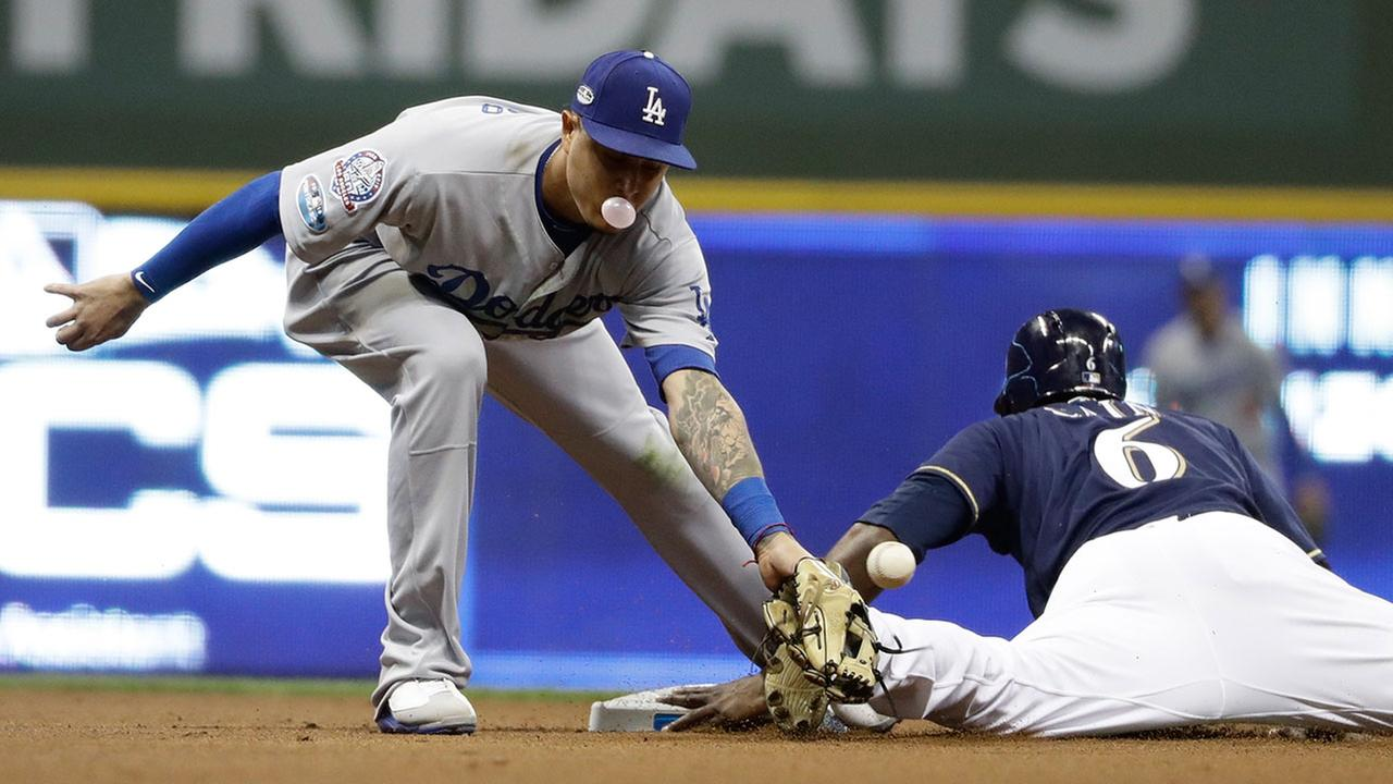 Milwaukee Brewers Lorenzo Cain steals second as Dodgers shortstop Manny Machado covers in Game 1 of the National League Championship Series in Milwaukee on Friday, Oct. 12, 2018.