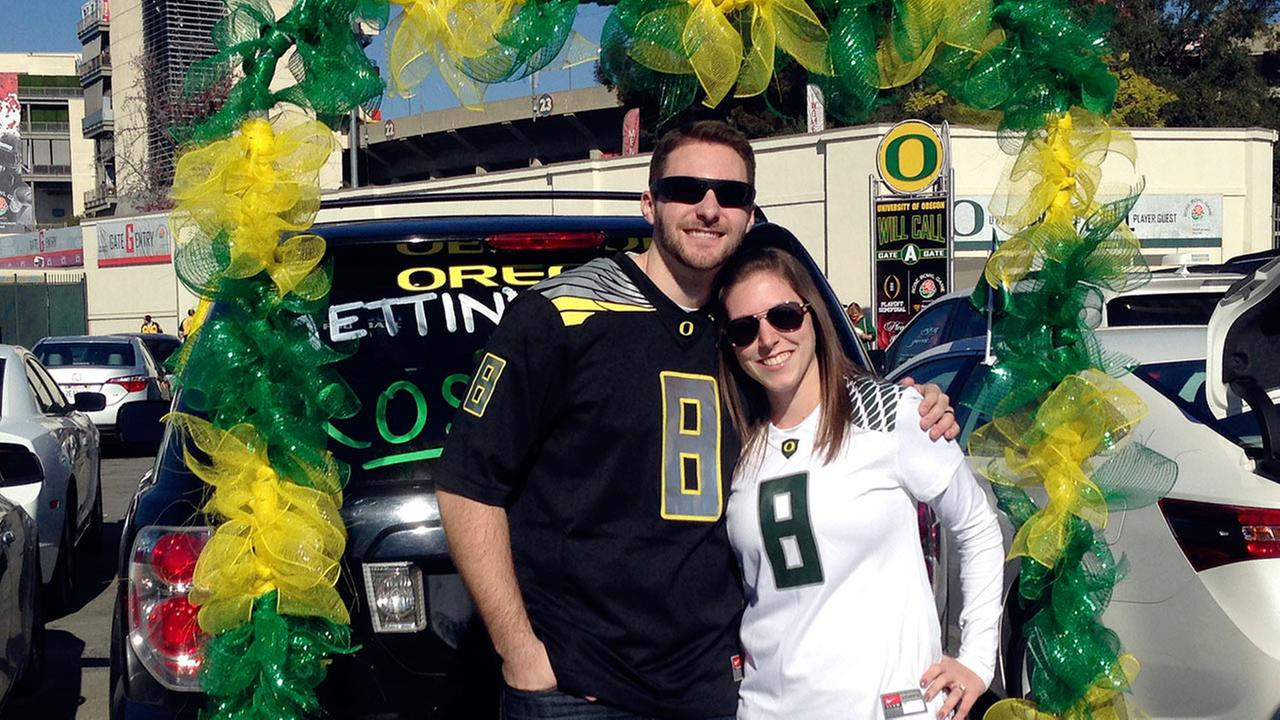 Oregon fans Steve Twomey and Lisa DeFluri pose for a photo outside the stadium before the Rose Bowl NCAA college football playoff semifinal game, Thursday, Jan. 1, 2015 in Pasadena, Calif.
