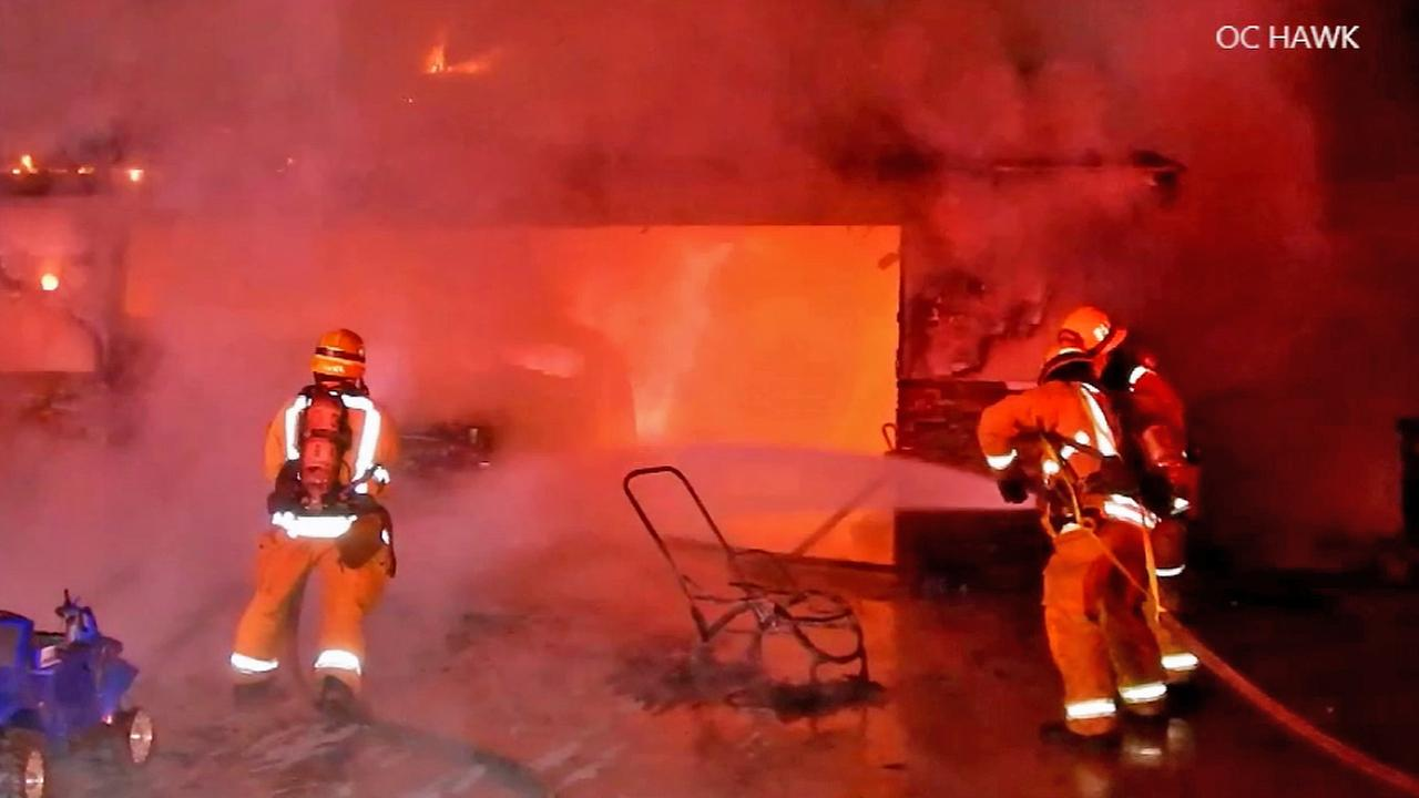 Firefighters work to put out a blaze in the garage of a home in Orange on Saturday, Jan. 3, 2015.