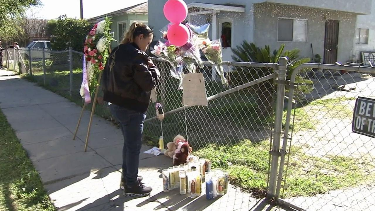 A woman leaves flowers at a makeshift memorial outside a home in the 100 block of West 51st in Long Beach where three people were shot Saturday, Jan. 3, 2015.
