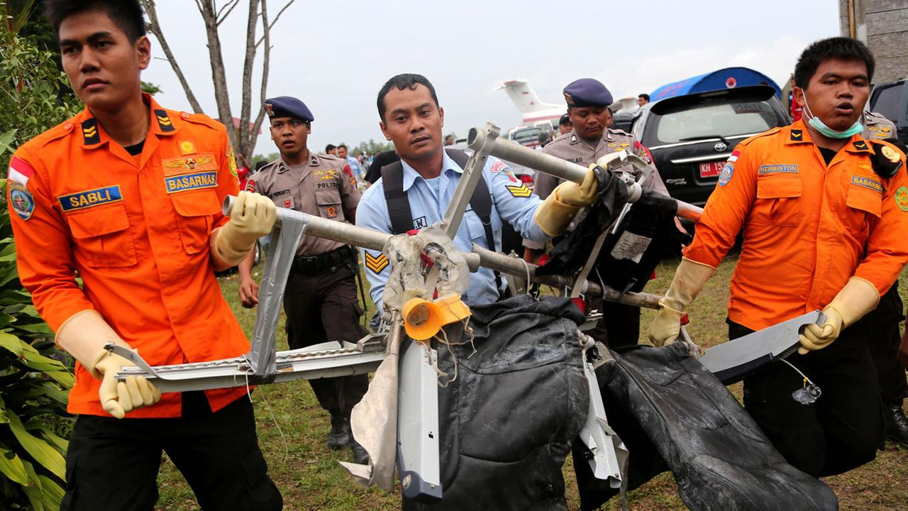 National Search and Rescue Agency personnel carry the seats of AirAsia Flight 8501 after being airlifted by a U.S. Navy helicopter, at the airport in Pangkalan Bun, Indonesia, Monday, Jan. 5, 2015.