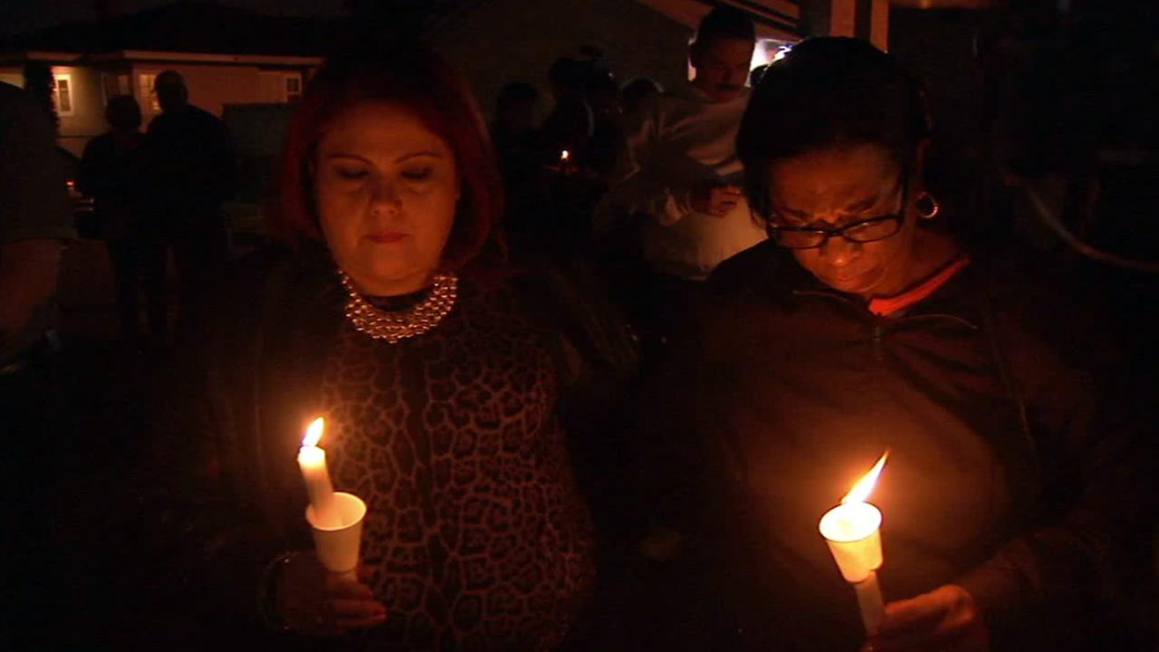 Two women bow their heads at a candlelight vigil held for a Long Beach baby found dead in a dumpster on Friday, Jan. 9, 2015.