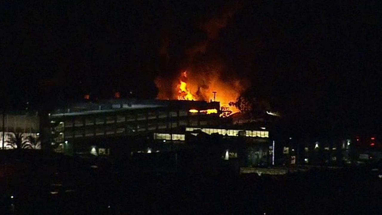 Flames burn through the roof of a Culver City commercial building on Friday, Jan. 16, 2015.