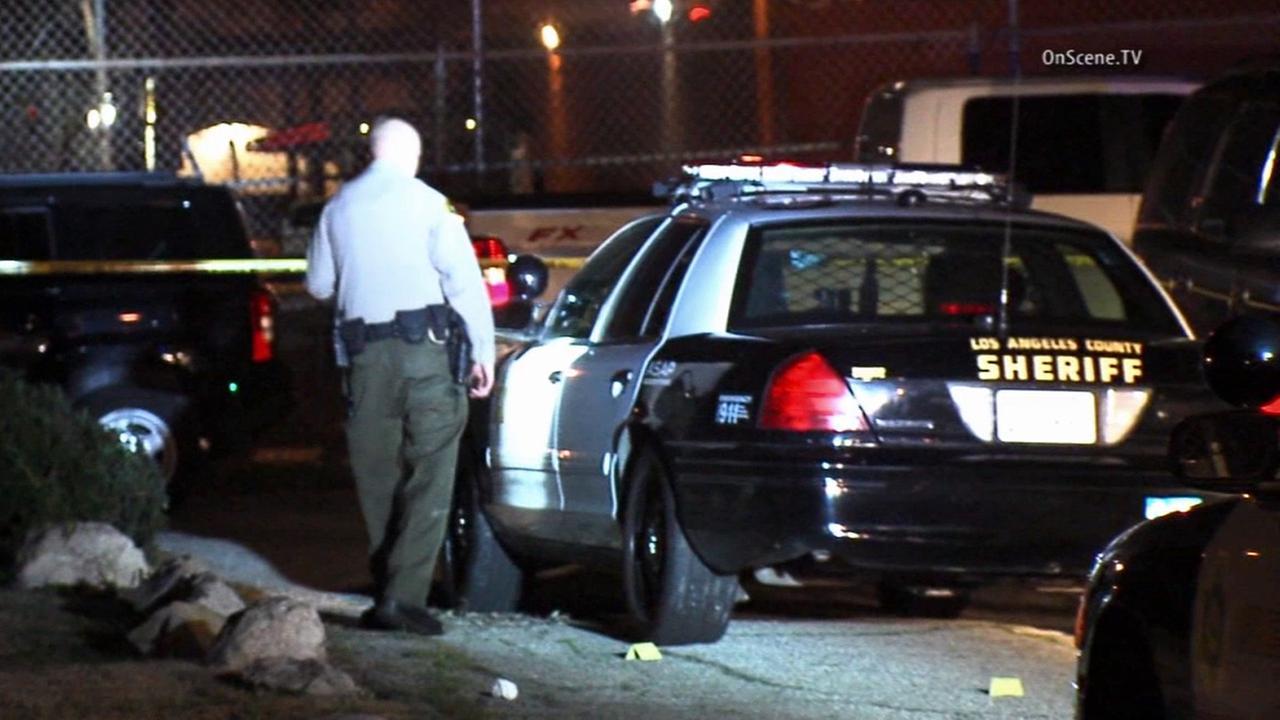 A Los Angeles County sheriffs deputy investigates the scene of a deputy-involved shooting in Lomita on Sunday, Jan. 18, 2015.