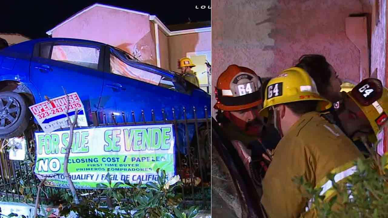Los Angeles firefighters rescued a woman whose car landed on top of a fence following a three-car collision in South Los Angeles Sunday, Feb. 1, 2015.