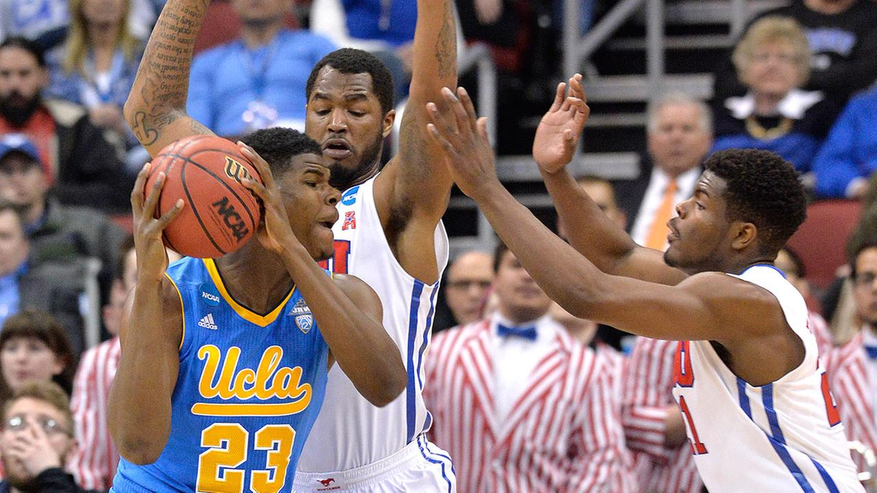UCLAs Tony Parker, left, looks for an opening against SMUs Ben Emelogu, right, and Markus Kennedy during the second round of the NCAA college basketball tournament in Louisville, Ky., Thursday, March 19, 2015.
