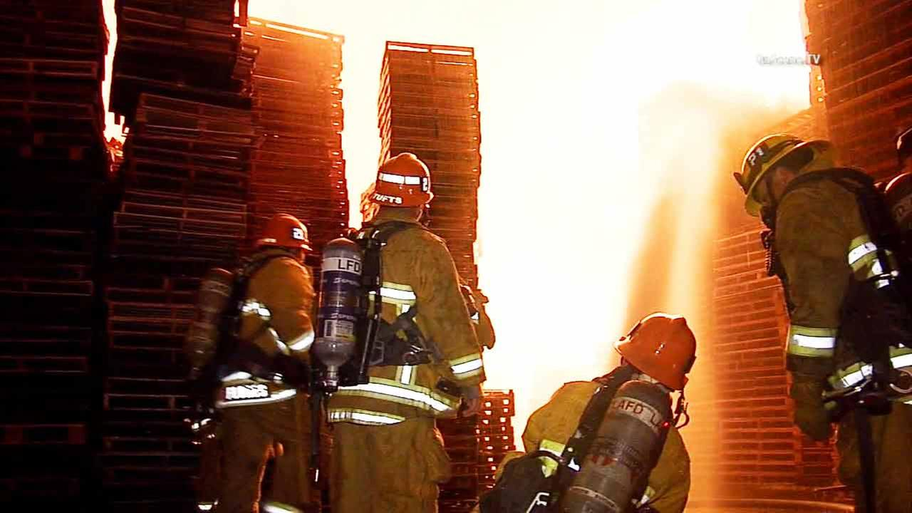 Firefighters battle a pallet yard fire on Long Beach Avenue and 48th Place in South Los Angeles on Friday, March 20, 2015.