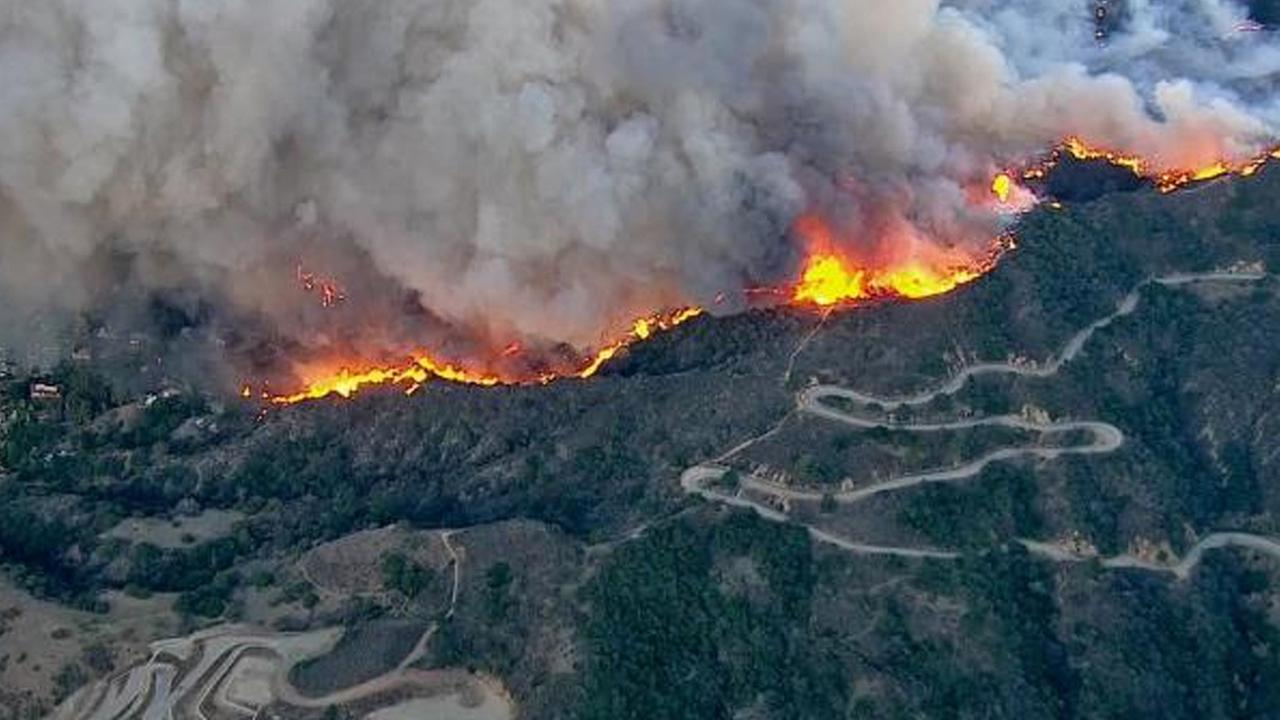 A brush fire is seen burning in the foothills above the Glendora and Azusa area on Thursday, Jan. 16, 2014
