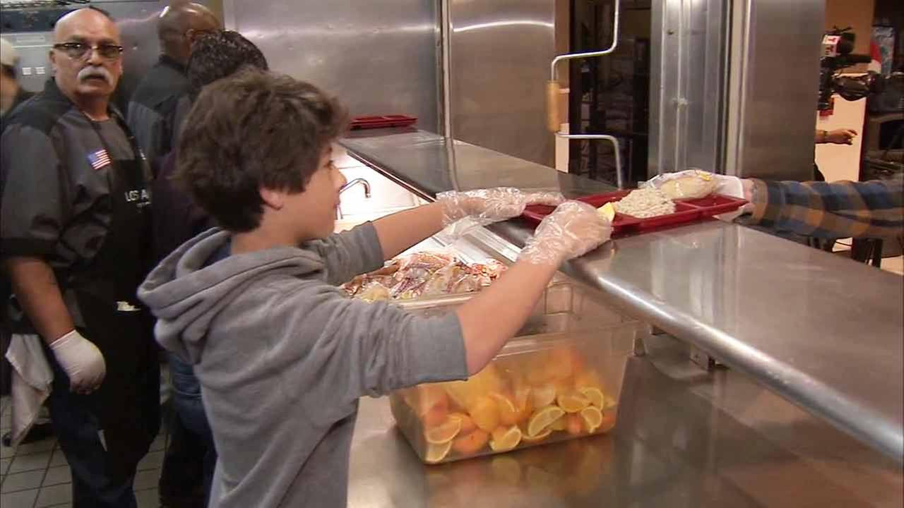A young volunteer serves meals at Los Angeles Mission on Friday, April 3, 2015.