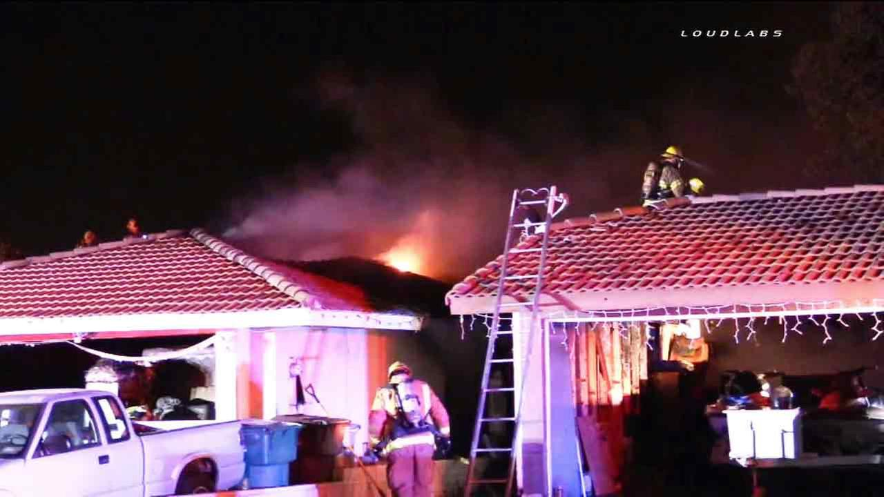 Firefighters battle a house fire that spread to an adjacent residence in Moreno Valley on Wednesday, April 16, 015.