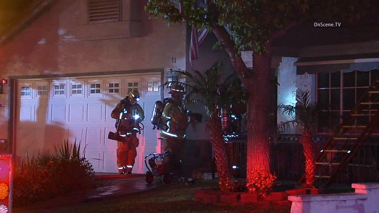 Firefighters work to put out a fire that broke out in a Pomona home on Friday, April 17, 2015.