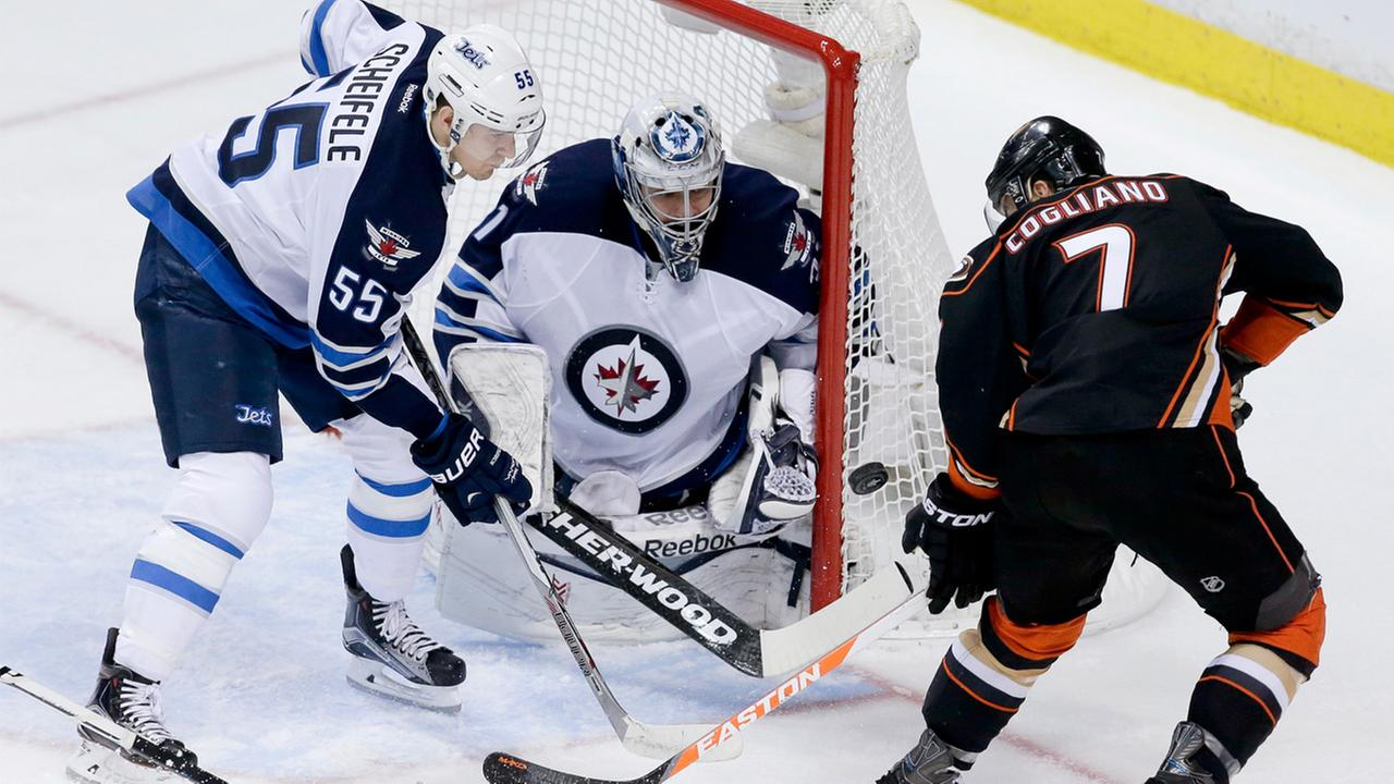 Winnipeg Jets goalie Ondrej Pavelec, middle, blocks a shot by Anaheim Ducks center Andrew Cogliano, right, as center Mark Scheifele helps defend during the first period of Game 2 of a first-round NHL hockey playoff series in Anaheim, Calif.