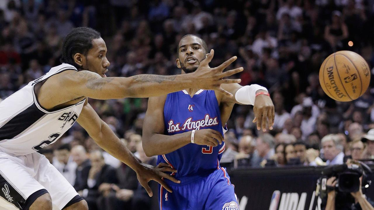 Los Angeles Clippers Chris Paul passes the ball around San Antonio Spurs Kawhi Leonard during Game 4 of NBA basketball playoff series, Sunday, April 26, 2015, in San Antonio.