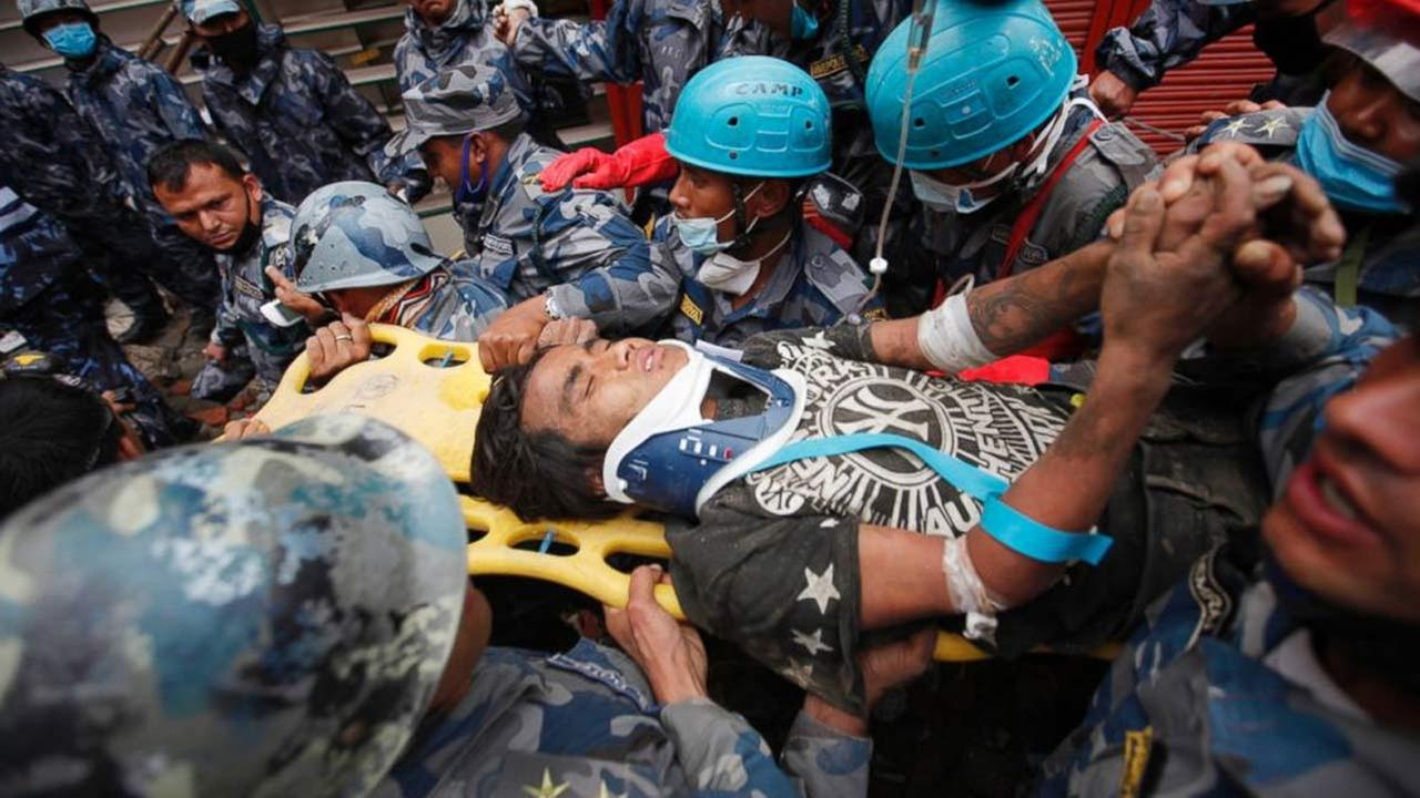 A survivor is carried on a stretcher after being rescued by Nepalese policemen and U.S. rescue workers from a building that collapsed five days ago in Nepal, April 30, 2015.