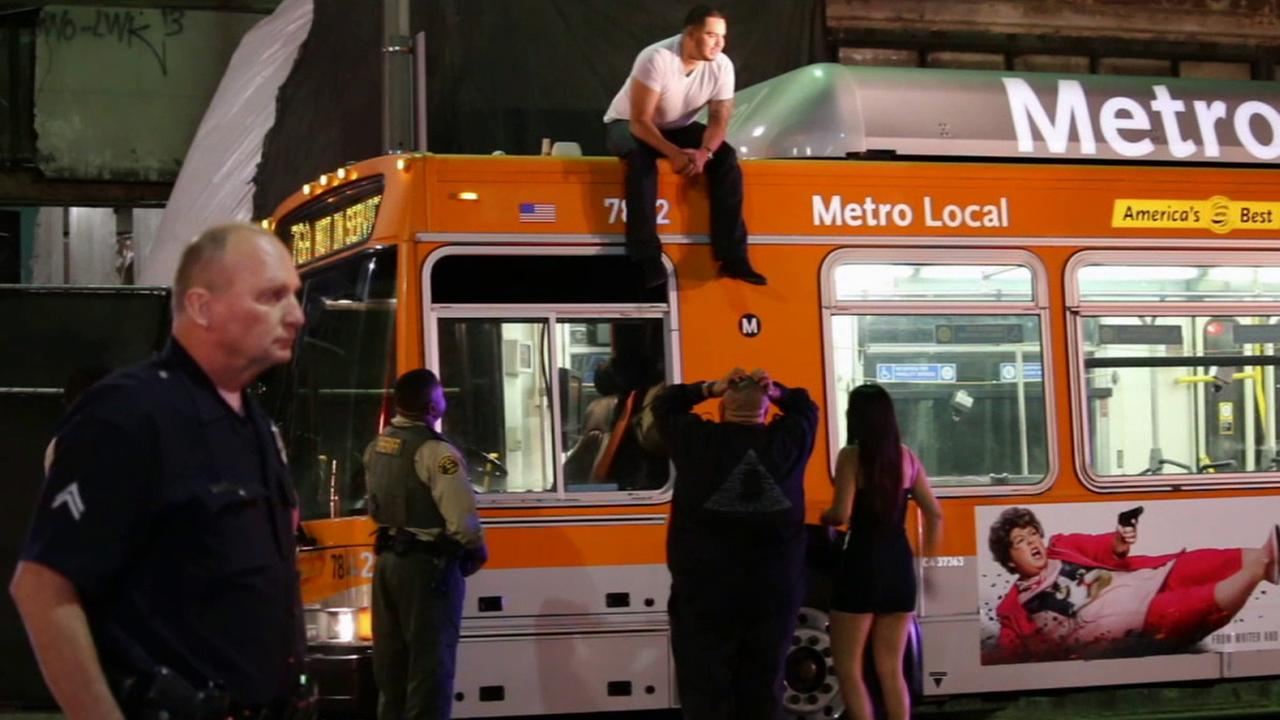 Friends and crisis negotiators attempt to coax a man who jumped on the roof of a Metro bus near 8th and Olive streets in downtown Los Angeles Sunday, May 3, 2015 to climb down.