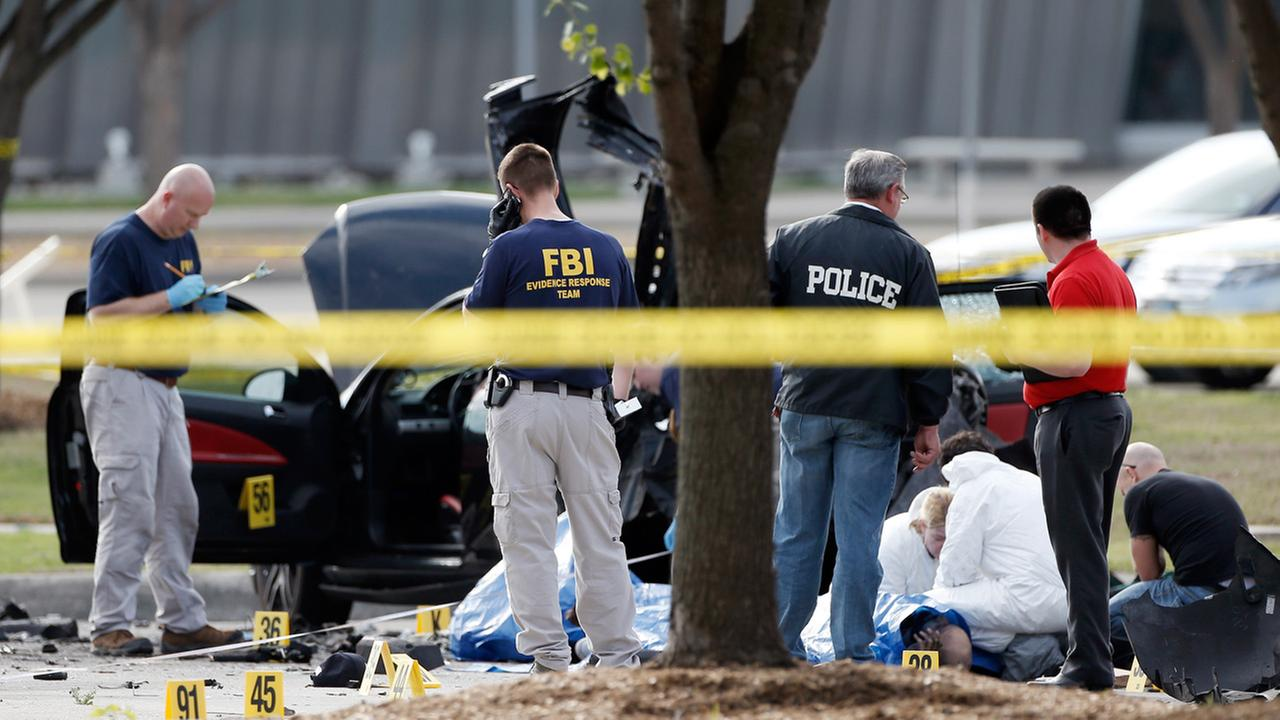 FBI crime scene investigators document the area around two deceased gunmen and their vehicle outside the Curtis Culwell Center in Garland, Texas, Monday, May 4, 2015.