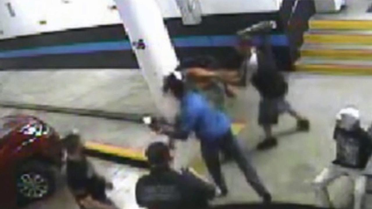 A Miami Beach police detective is shown punching a handcuffed woman in the face in surveillance footage.