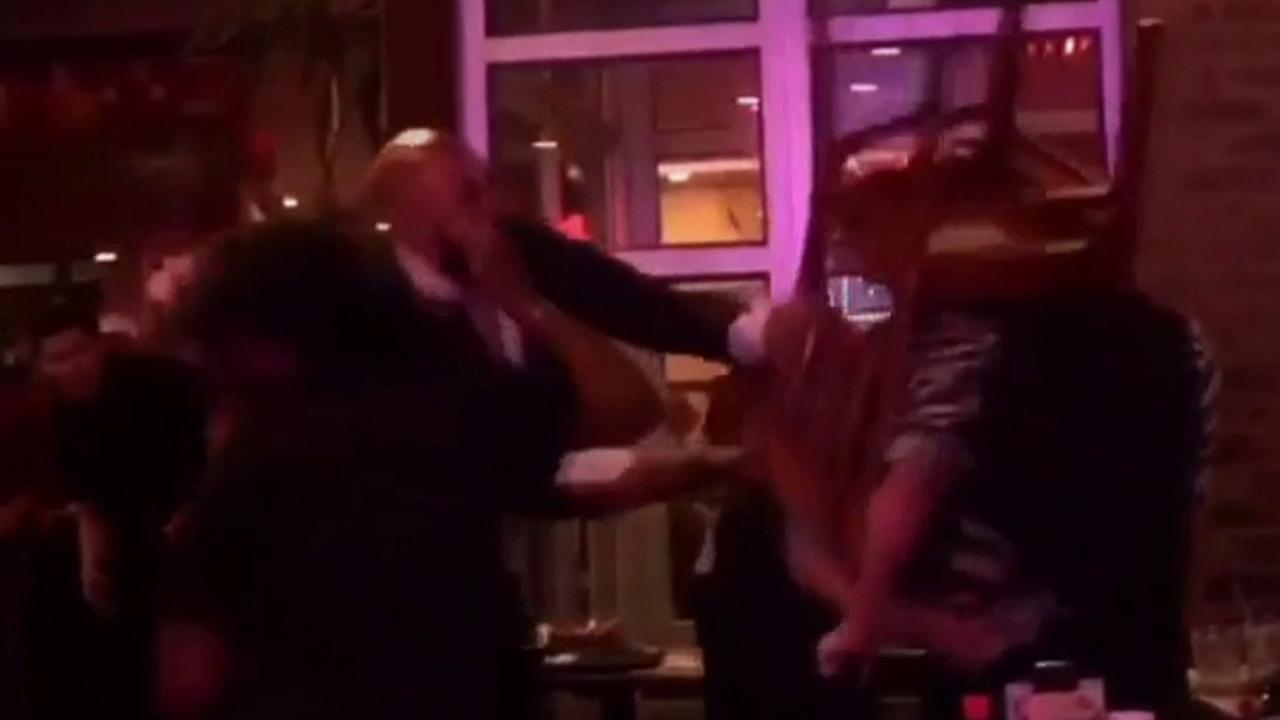 A man is shown hitting another man with a chair in surveillance video from inside a New York City restaurant.