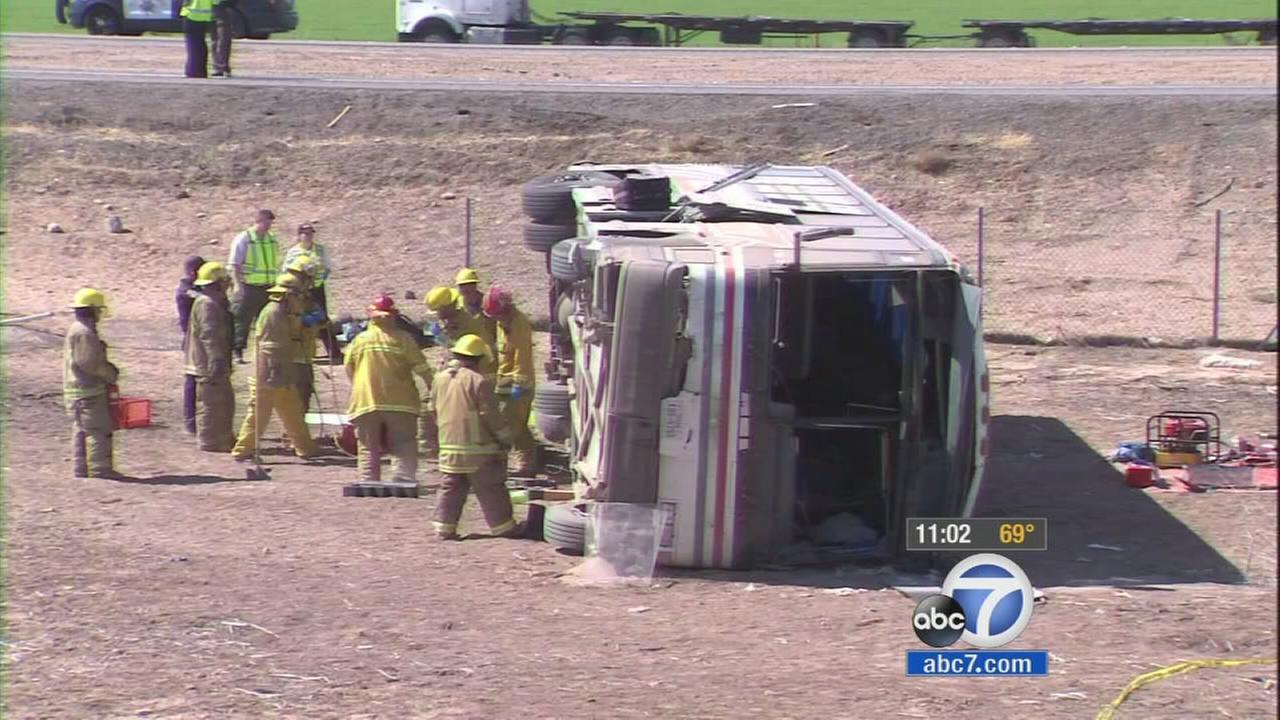 Firefighters work on moving a bus that overturned on the I-10 Freeway near the Arizona border on Wednesday, May 21, 2014.