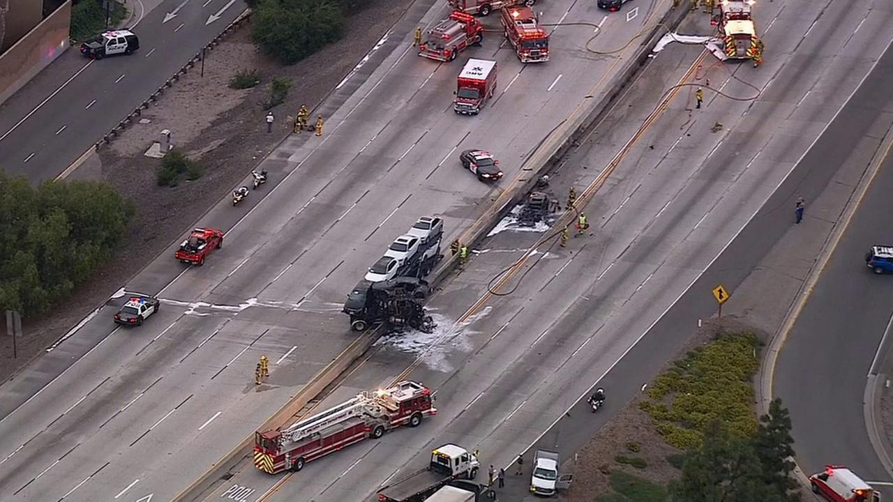 Firefighters use foam to douse any remaining flames on a car and semi-truck hauling cars on the 210 Freeway in Arcadia on Monday, May 18, 2015.