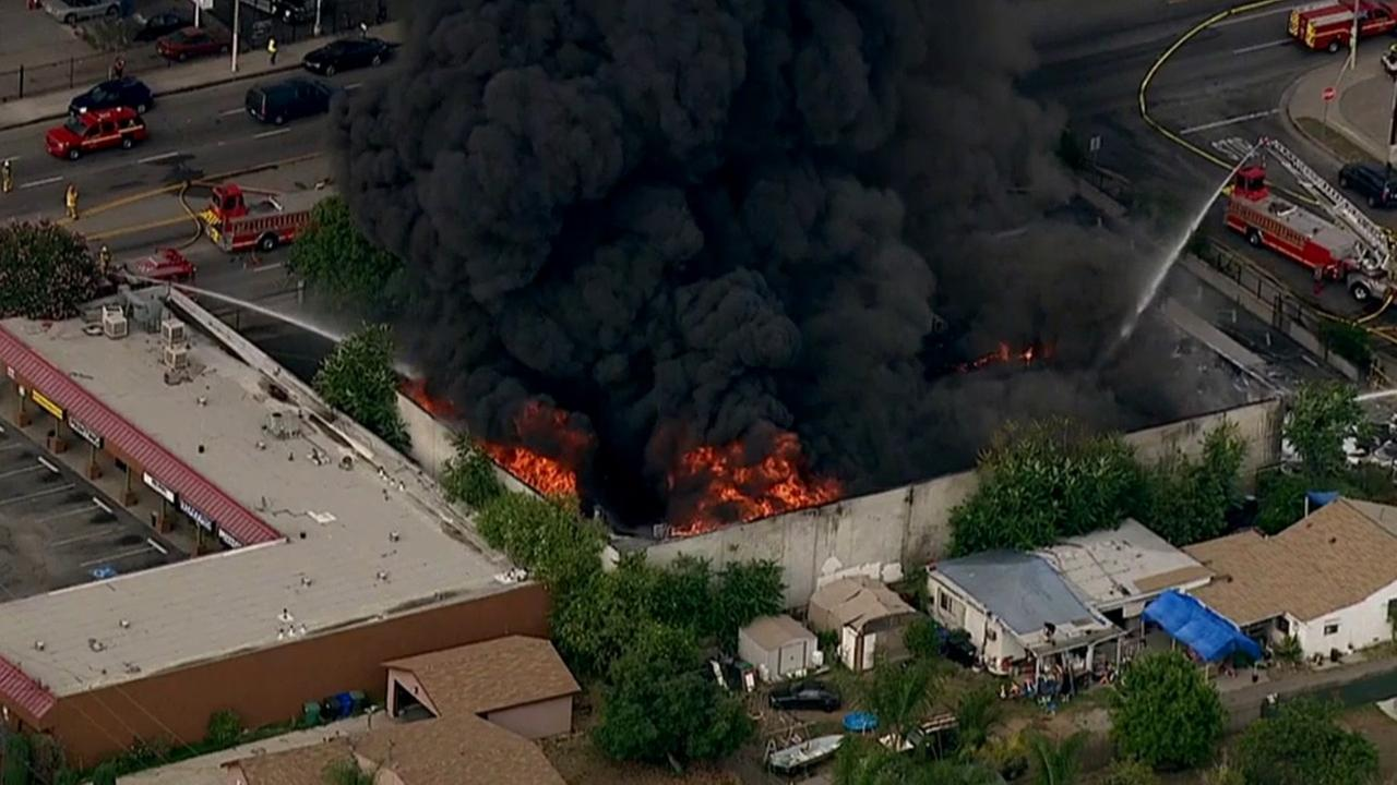 Los Angeles County firefighters work to put out flames that broke out at a commercial building in the City of Industry, Friday, June 12, 2015.