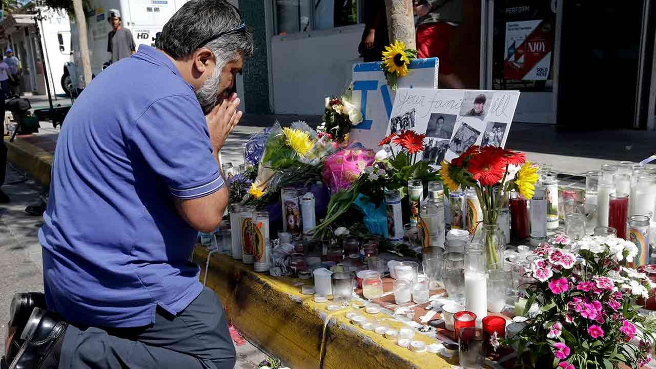 Jose Cardoso pays his respects at a makeshift memorial in front of the IV Deli Mart, where part of Friday nights mass shooting took place by a drive-by shooter.
