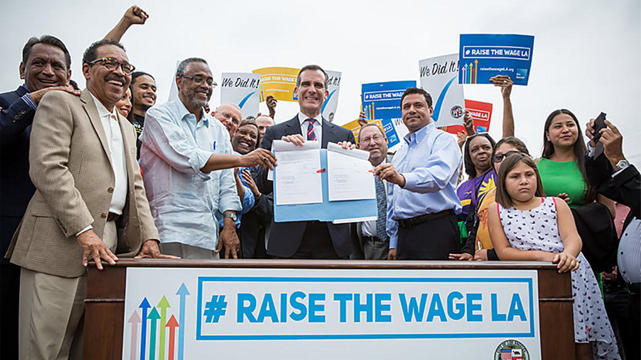 Los Angeles Mayor Eric Garcetti signs into law an ordinance to raise the minimum wage to $15 an hour by 2020.