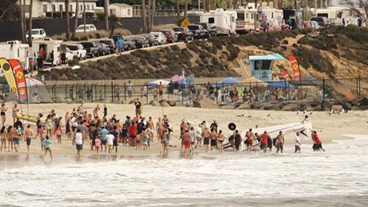 A small plane that may have been towing an advertising banner crashed into the ocean and ended up on a beach in Carlsbad on Saturday, July 4, 2015.